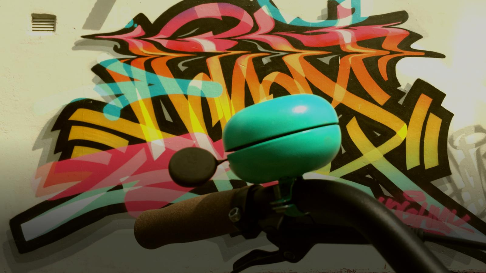 smart bicycle bell on handlebars in front of stylish graffiti