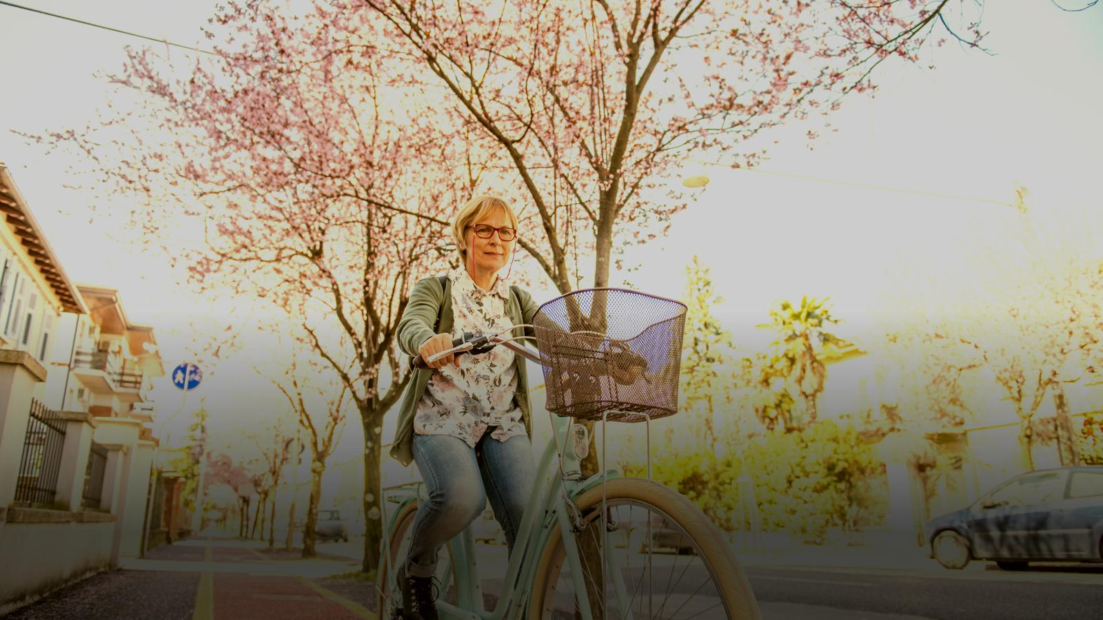 woman cycling along street with cherry blossom